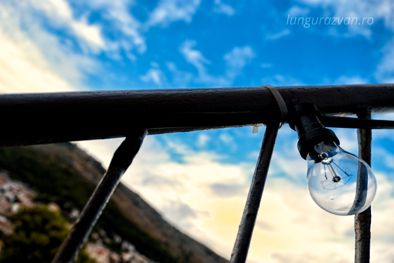 Waiting for His Time, Blue sky behind light bulb attached to handrail
